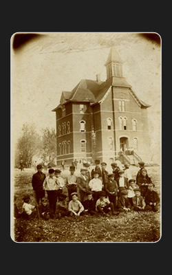 Picture of the school with Children in front of it.